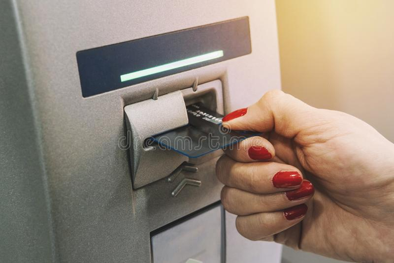 Woman hand inserting credit card to ATM. girl gets paid from an ATM. The card comes out of the terminal. royalty free stock photography