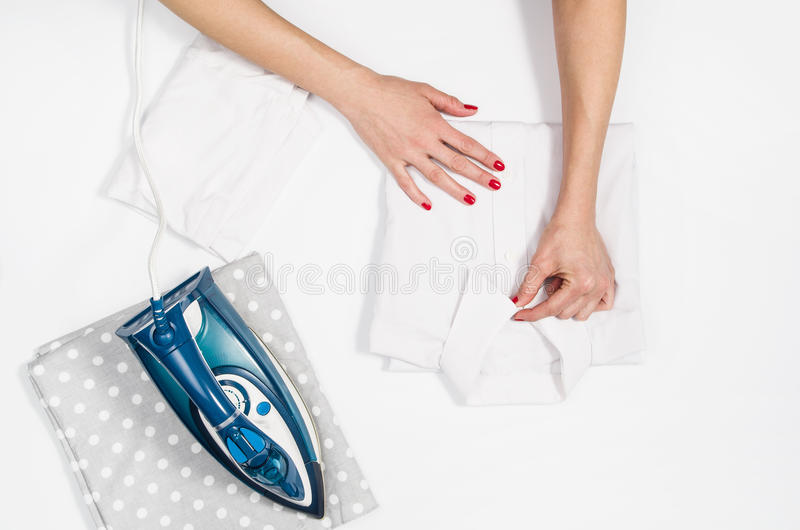 Woman hand ironing clothes top view isolated on white background stock photography