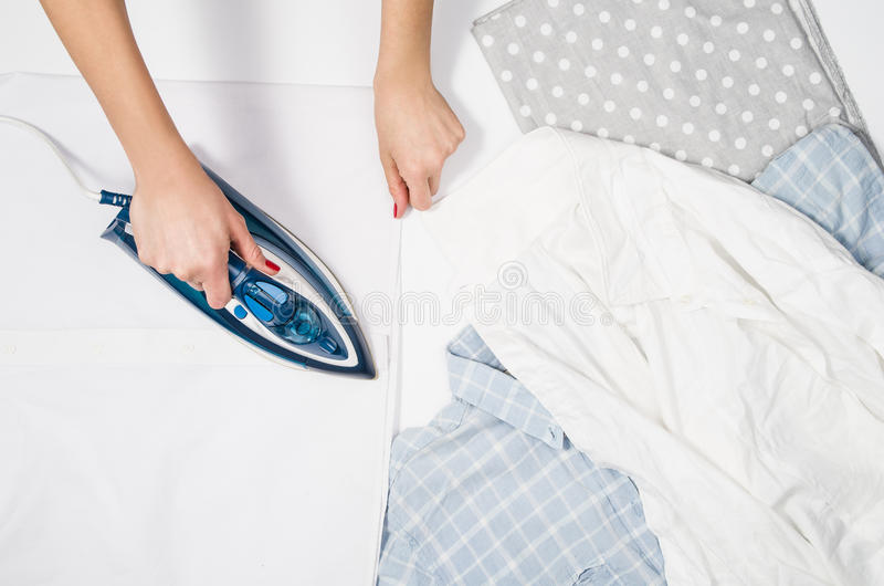 Woman hand ironing clothes top view on white background royalty free stock images