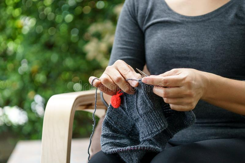 Woman hand knitting in a garden royalty free stock photo