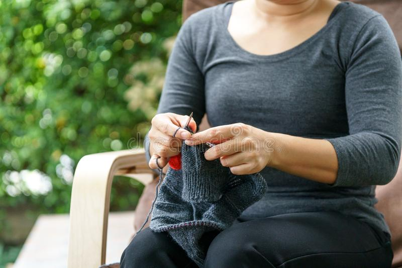 Woman hand knitting in a garden stock image