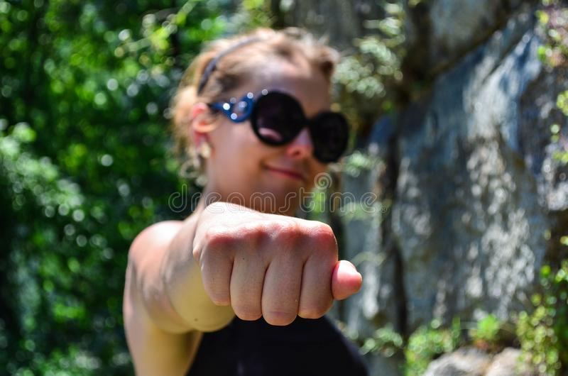Woman with hand in a knuckle fist position. Smug smile, defocused. Selective focus intentionally on fist. Concept for fighting,. Champion, winner royalty free stock photos