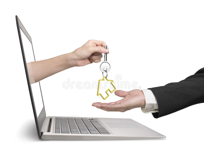 Woman hand from laptop giving house key to man hand. Woman hand from laptop screen giving house key to man hand, real estate online for sale or for rent royalty free stock photo