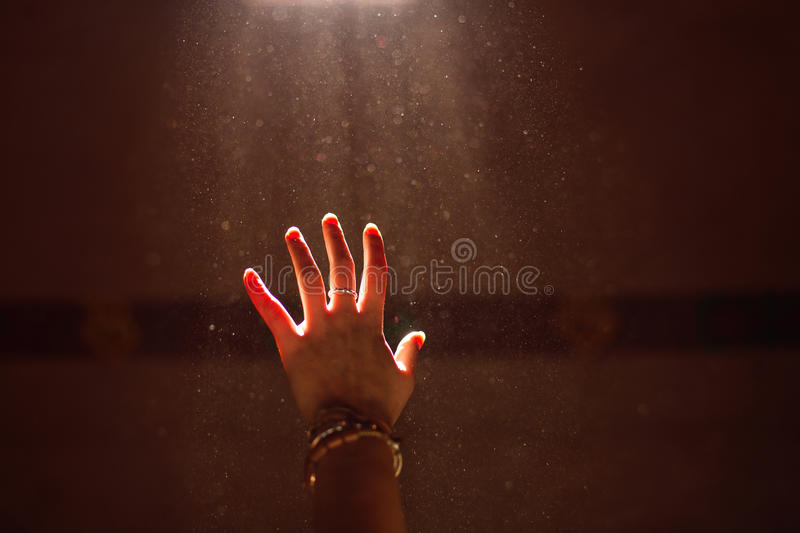 Woman hand into the light stock photos