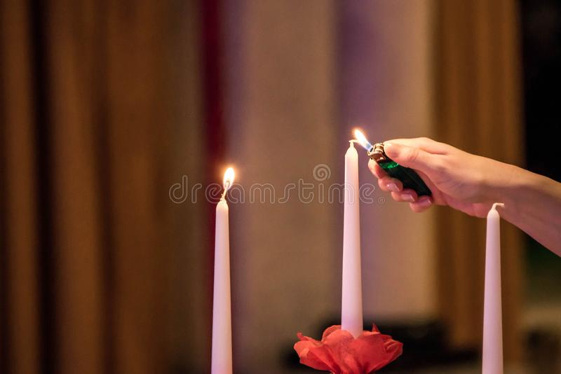 Woman hand lightning candles on Banquet with red table setting stock photography