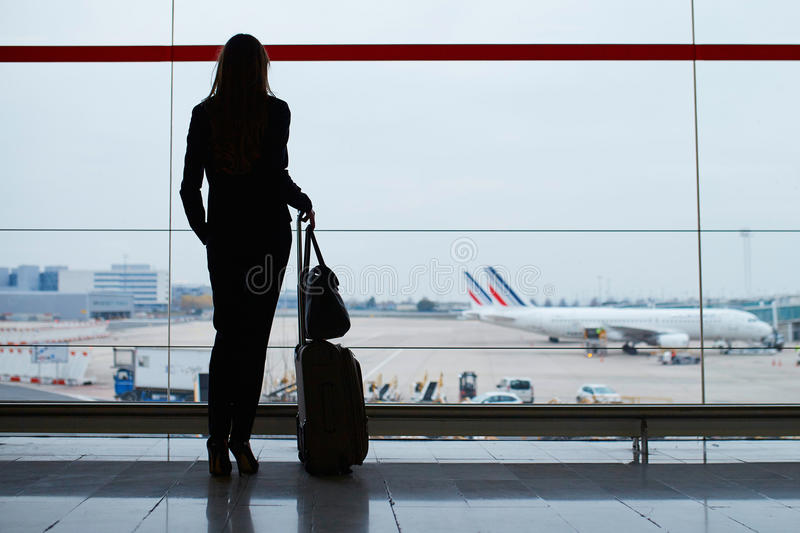Woman with hand luggage in international airport, looking through the window at planes stock photography