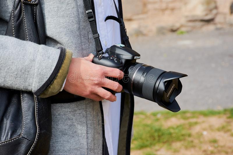 Woman hand with Nikon camera and tamron lens. Andernach, Germany - September 26, 2018: Black DSLR camera,Nikon D7200 with Tamron lens in young woman`s hand stock images