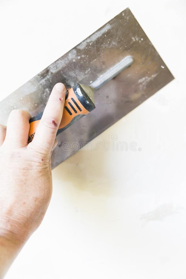 Woman hand with old metal spatula to equalize plaster filler on the wall. Close-up of a woman hand with metal big spatula, to equalize the plaster filler on the stock photography