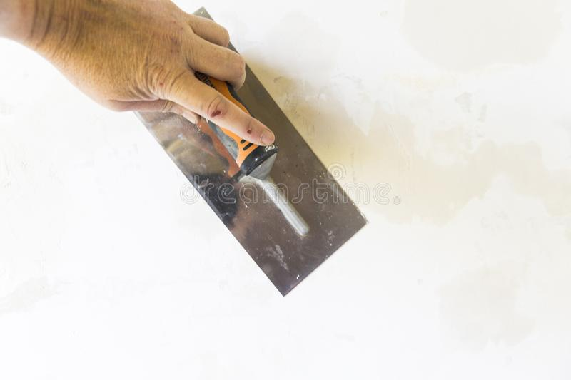 Woman hand with old metal spatula to equalize plaster filler on the wall. Close-up of a woman hand with metal big spatula, to equalize the plaster filler on the stock image