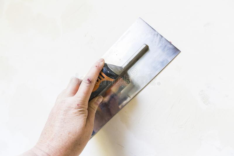 Woman hand with old metal spatula to equalize plaster filler on the wall. Close-up of a woman hand with metal big spatula, to equalize the plaster filler on the royalty free stock photography