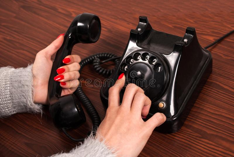 Woman hand and old phone on wooden desk. Finger dial telephone numbers royalty free stock photos