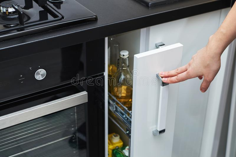 Woman hand open a kitchen storage cabinet in modern interior. Woman hand open kitchen storage cabinet in modern interior royalty free stock photography
