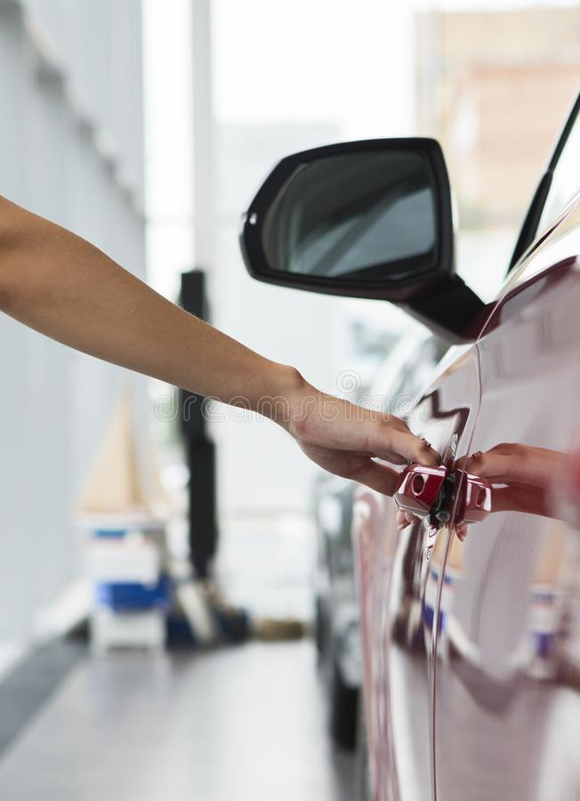 Woman hand on open the new red car door background stock photo