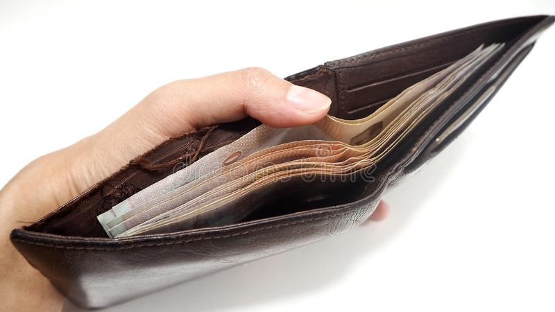 Woman hand open old brown leather wallet with has Thai banknotes inside. Money expense and saving concept stock image