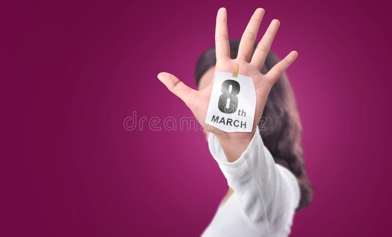 Woman hand with open palm showing 8 March on the paper note royalty free stock photography