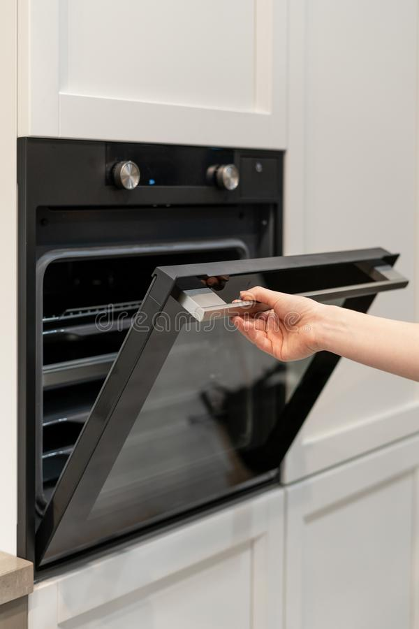 Woman hand opening black built-in oven in white kitchen cabinet. Vertical and real photo of woman hand opening door of new black built-in oven in white kitchen royalty free stock photos
