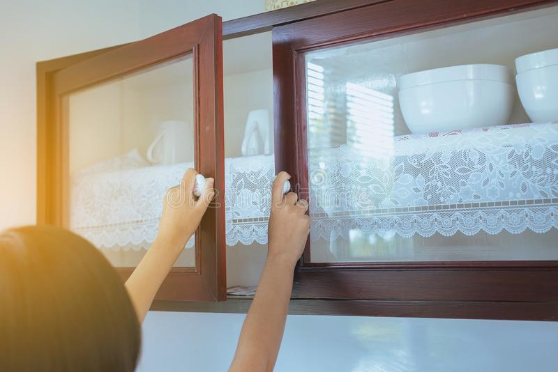 Woman with hand opening Built-in cabinet interior decoration in kitchen. Asian woman with hand opening Built-in cabinet interior decoration in kitchen royalty free stock photo