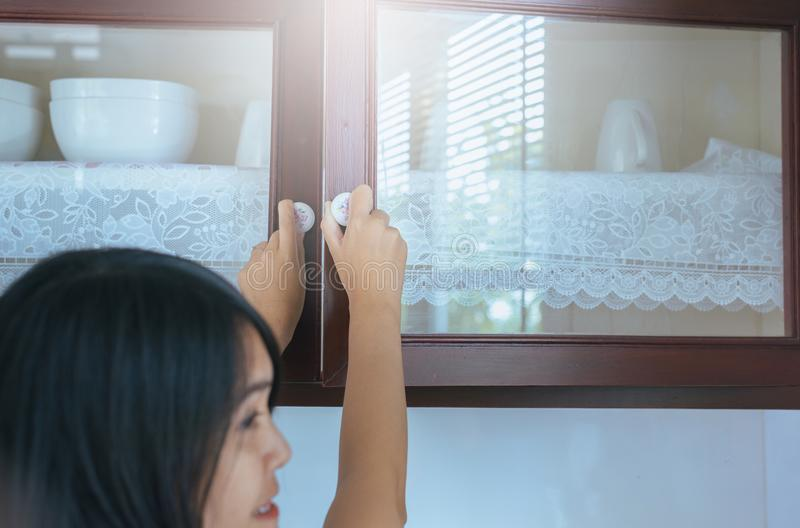 Woman with hand opening Built-in cabinet interior decoration in kitchen. At home royalty free stock image