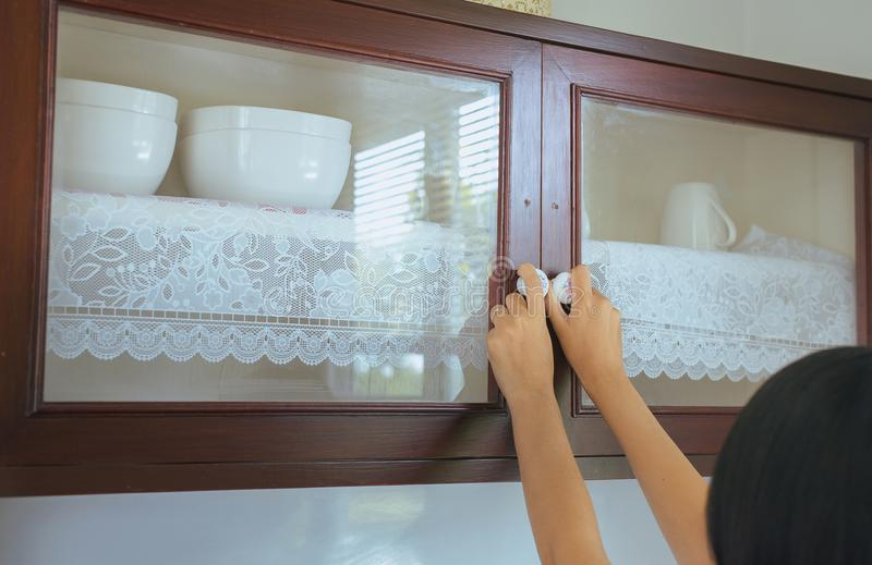 Woman with hand opening Built-in cabinet interior decoration in kitchen. At home royalty free stock photo