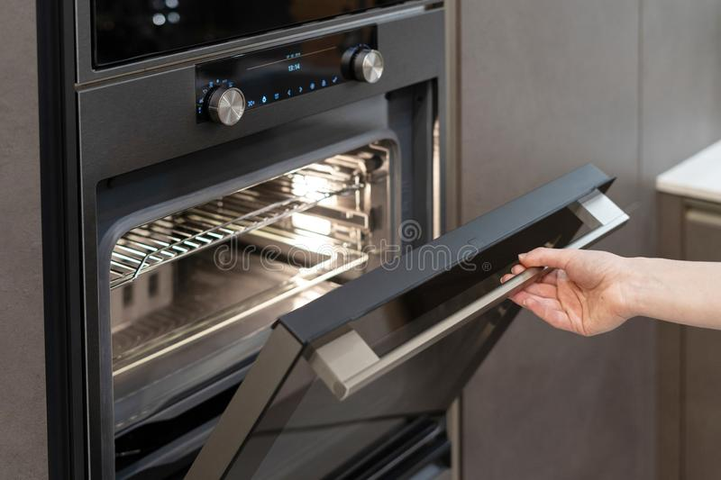 Woman hand opening built-in oven in black kitchen cabinet. Sedie view photo of woman hand opening new modern built-in oven in black kitchen cabinet royalty free stock photography