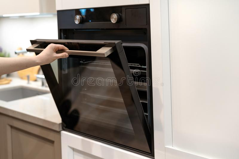 Woman hand opening built-in oven in white kitchen cabinet. Woman hand opening door of new modern built-in oven in white kitchen cabinet royalty free stock images