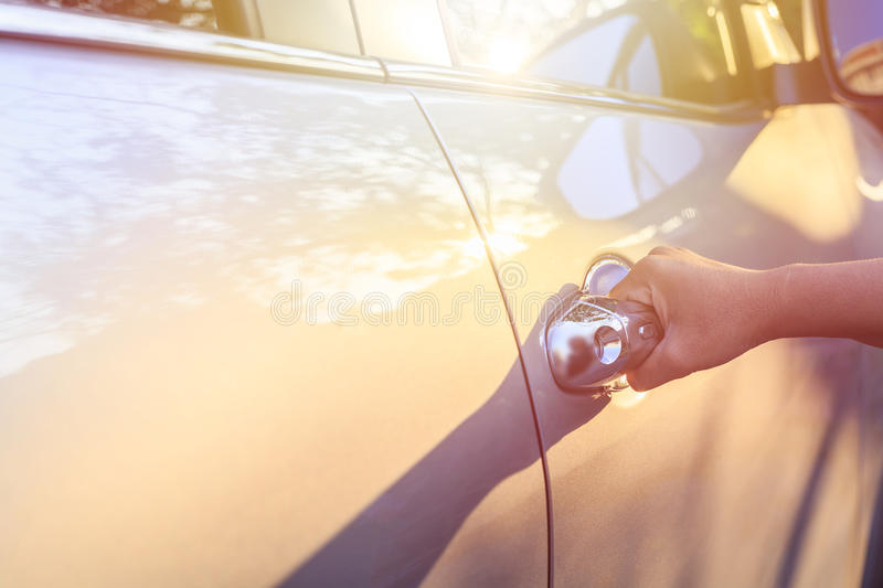 Woman hand opening car door. Shot at evening with lens flare stock photo