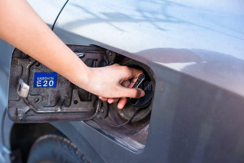 Woman hand opening car gas tank cap at petrol station. Woman opening car gas tank cap at petrol station stock images