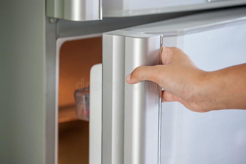 Woman hand opening refrigerator door royalty free stock photo