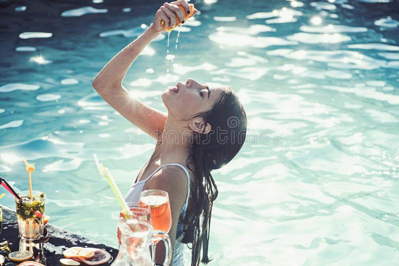 Woman hand with orange and cocktail glass near swimming pool. royalty free stock images