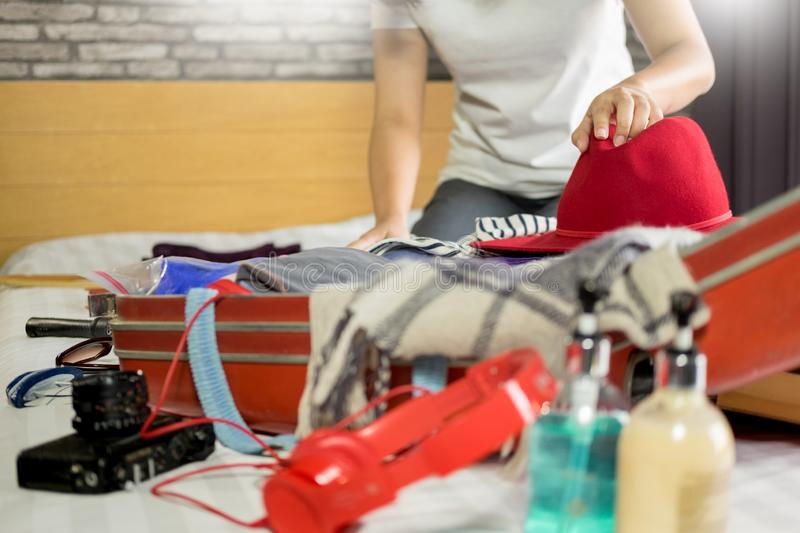 Woman hand packing a luggage for a new journey and travel for a long weekend stock photo
