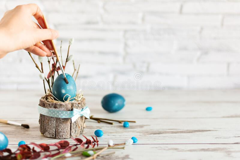 Woman hand paint Easter egg with paintbrush in modern marble classic blue color on wooden table. Happy Easter time stock photography