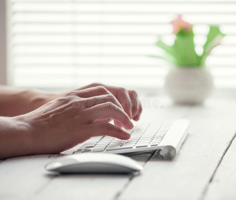 Woman hand on the PC keyboard stock photography