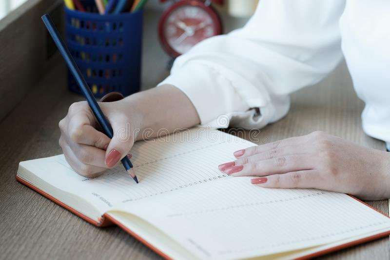 Woman hand with pencil writing on notebook. making notes in notebook with pencil. People writing on notebook and work on wooden royalty free stock photos