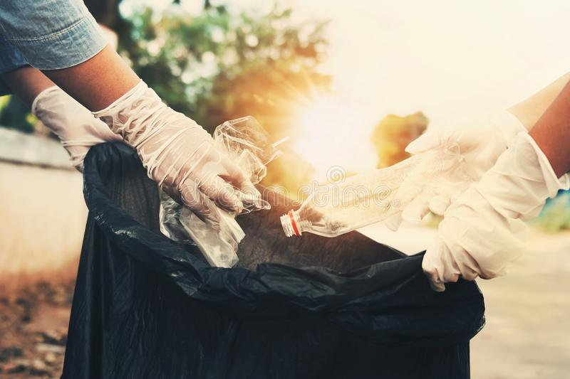 Woman hand picking up garbage plastic bottle for cleaning. At royalty free stock photos