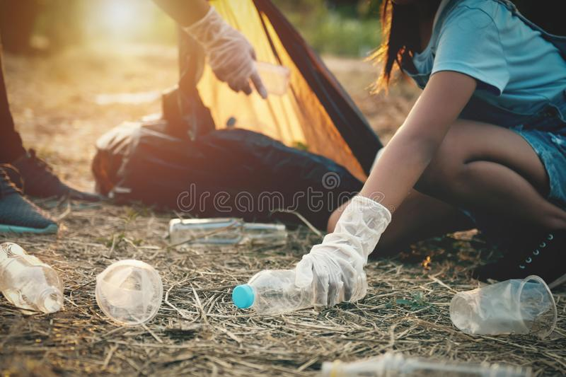 Woman hand picking up garbage plastic bottle for cleaning. At park stock photo