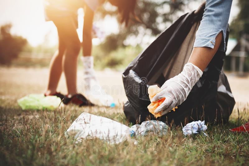 Woman hand picking up garbage plastic for cleaning. At park stock photos