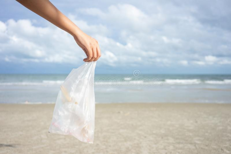 Woman hand picking up used plastic bag on sand beach, cleaning seaside beach.  Environmental pollution, Ecological problem and stock photos