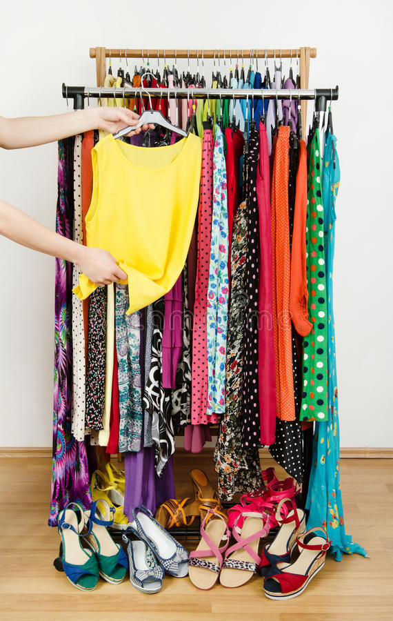 Woman hand picking up a yellow blouse to wear. stock images