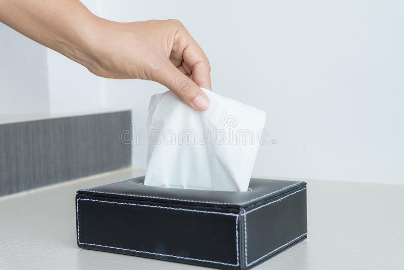 Woman hand picking white tissue paper . Woman hand picking white tissue paper from tissue box at home royalty free stock photo