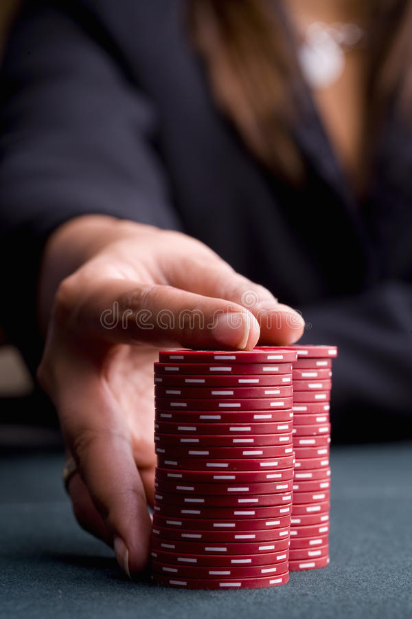 Woman with hand on pile of gambling chips, close-up of hand stock photos