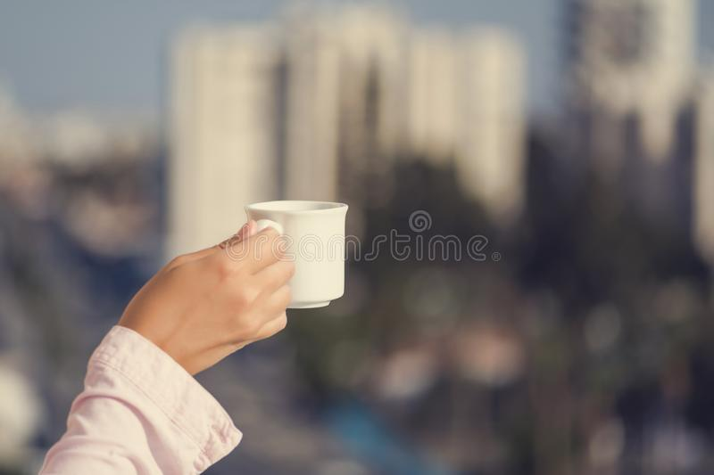 Woman hand in a pink shirt with cup of coffee at the summer morning against the background of town stock photo