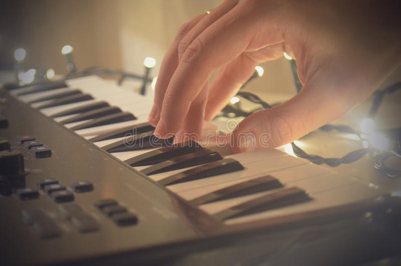 Woman hand playing Piano or electone midi keyboard, electronic musical synthesizer white and black key. royalty free stock image