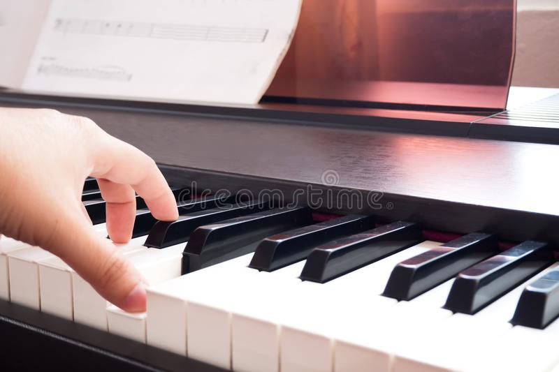 Woman hand playing piano. Music and art background. Back side vi stock photography