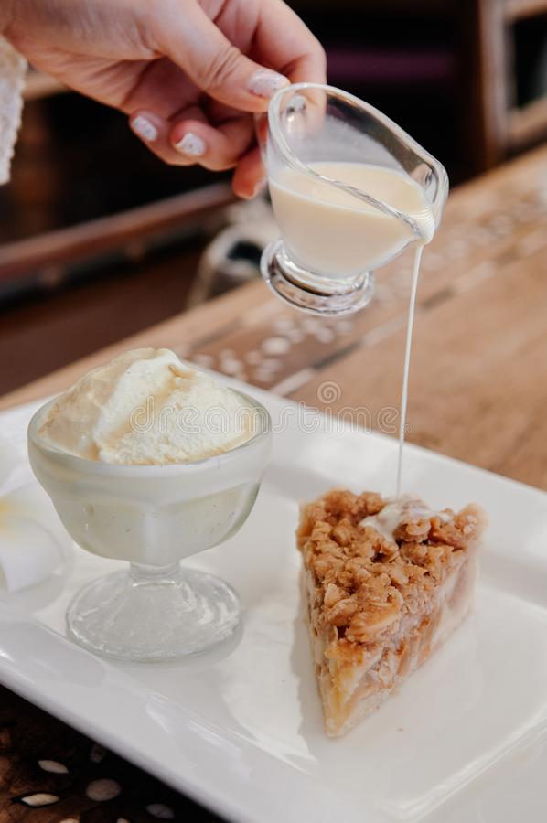 Pouring vanilla sauce on apple crumble pie with ice cream royalty free stock image