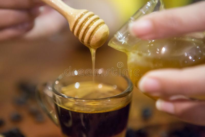 Woman hand pouring honey in a cup of coffee. Close up of Woman hand pouring honey in a cup of coffee royalty free stock image