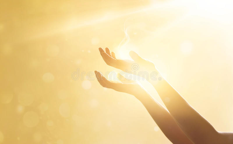 Woman hand praying for blessing from god on sunset stock photo