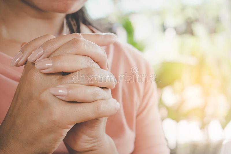 Woman hand praying peacefully outdoors. In the morning with sunlight background royalty free stock images