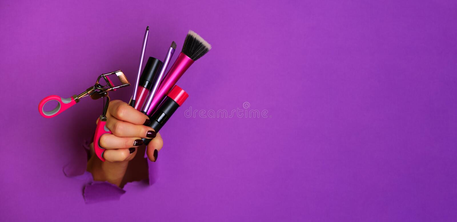 Woman hand with professional cosmetic tools for make up: brushes, mascara, lipstick, eyelash curler on violet background. Beauty royalty free stock images