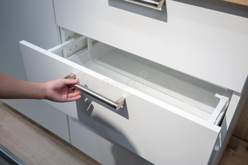 Woman hand pulling a drawer organized with additional plastic royalty free stock photo