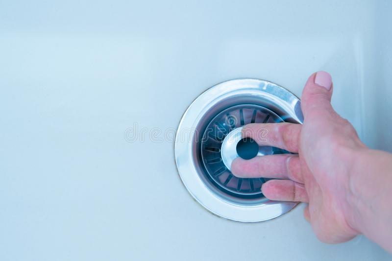 Woman hand pulls close cap of drainage hole of sink to drain water stock photo